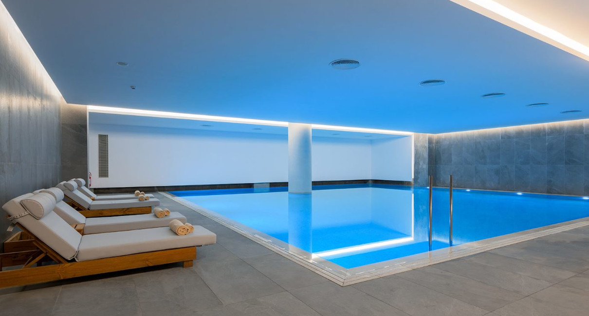 Spacious indoor spa pool with loungers