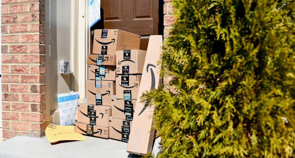 Amazon boxes and parcels stacked outside front door
