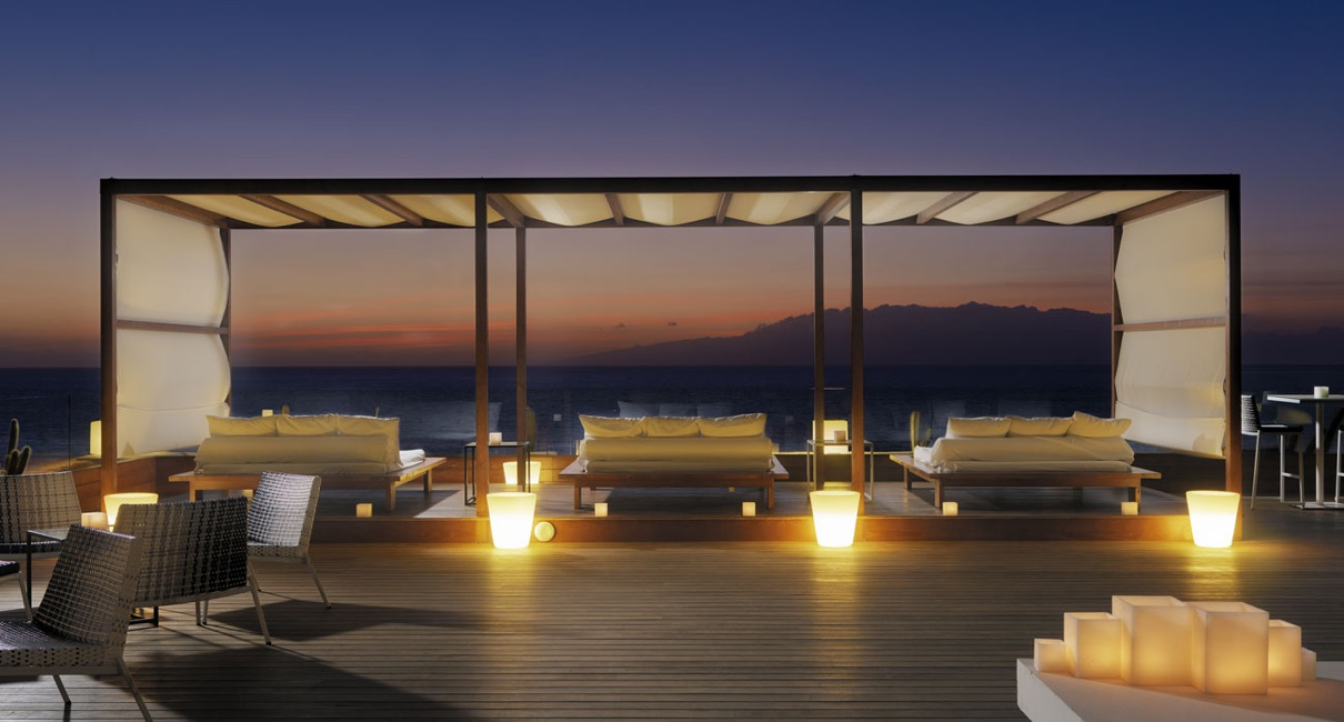 Candle-lit terrace at night with sun loungers