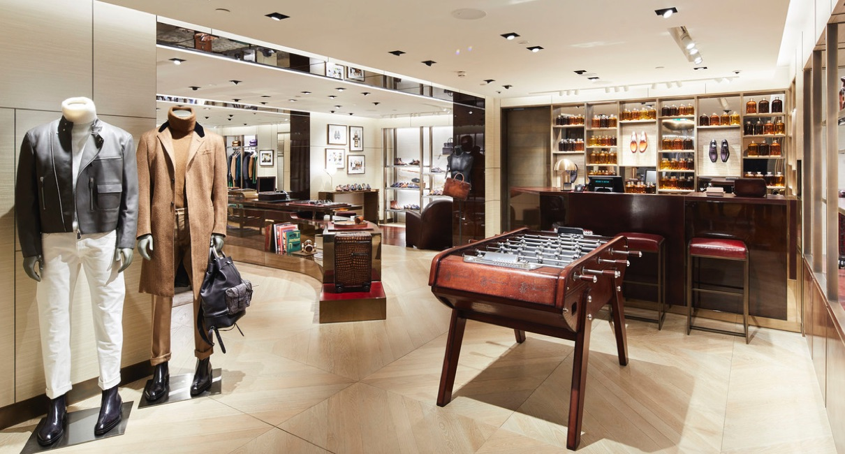 Beluti menswear area with a dark wood foosball table and mannequins wearing luxury garments
