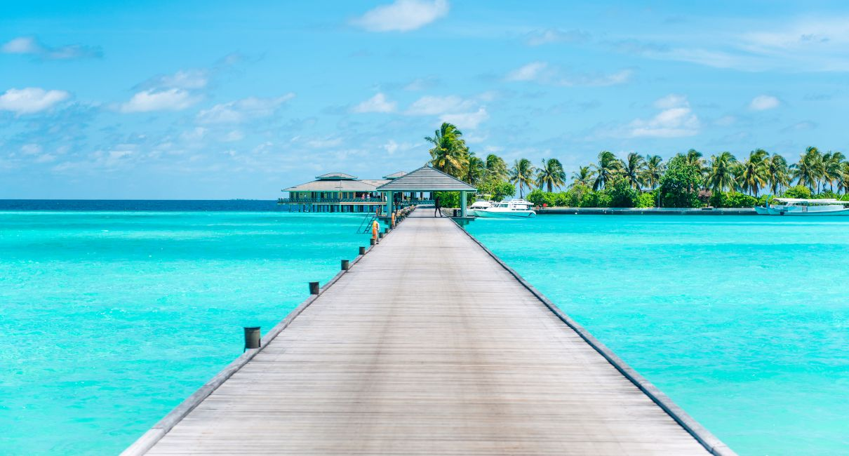 Maldives pier with a seaplane, crystal blue waters and jet skis