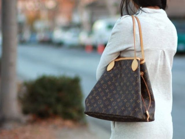 Woman walks down a suburban street with Louis Vuitton bag over her shoulder