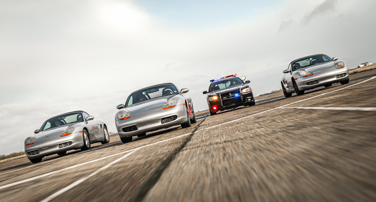 Three Porsche Boxter sports cars being pursued by a Dodge Charger sheriff car