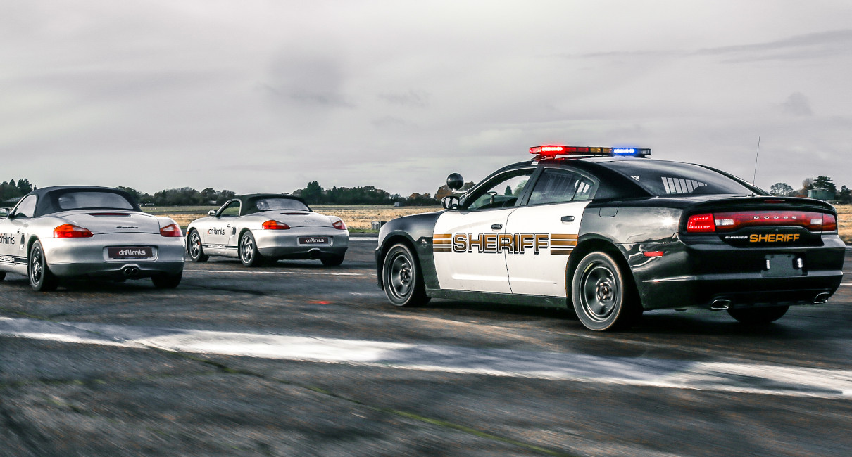 Dodge Charger police car chases 2 Porsche Boxters
