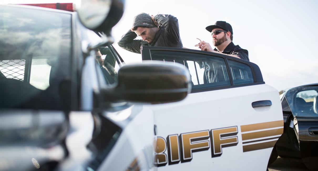 Getaway driver is escorted into police car by cop