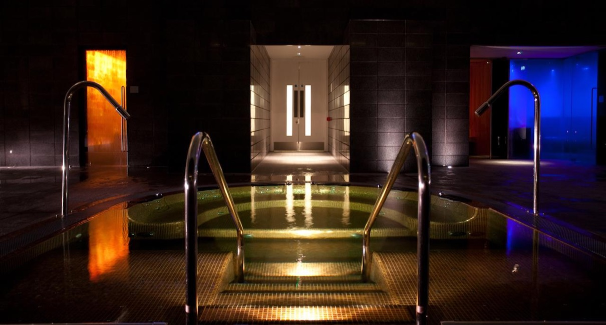 Luxury relaxation jacuzzi spa pool in a dark room with steam room and sauna