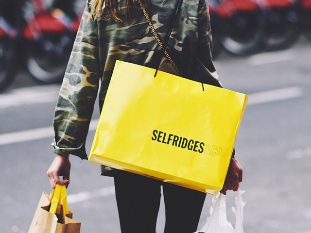 Woman walking away with Selfridges bag over her shoulder