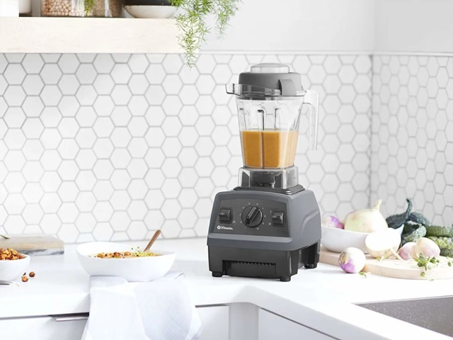 Vitamix E310 blender sits on kitchen counter with food being prepared next to it